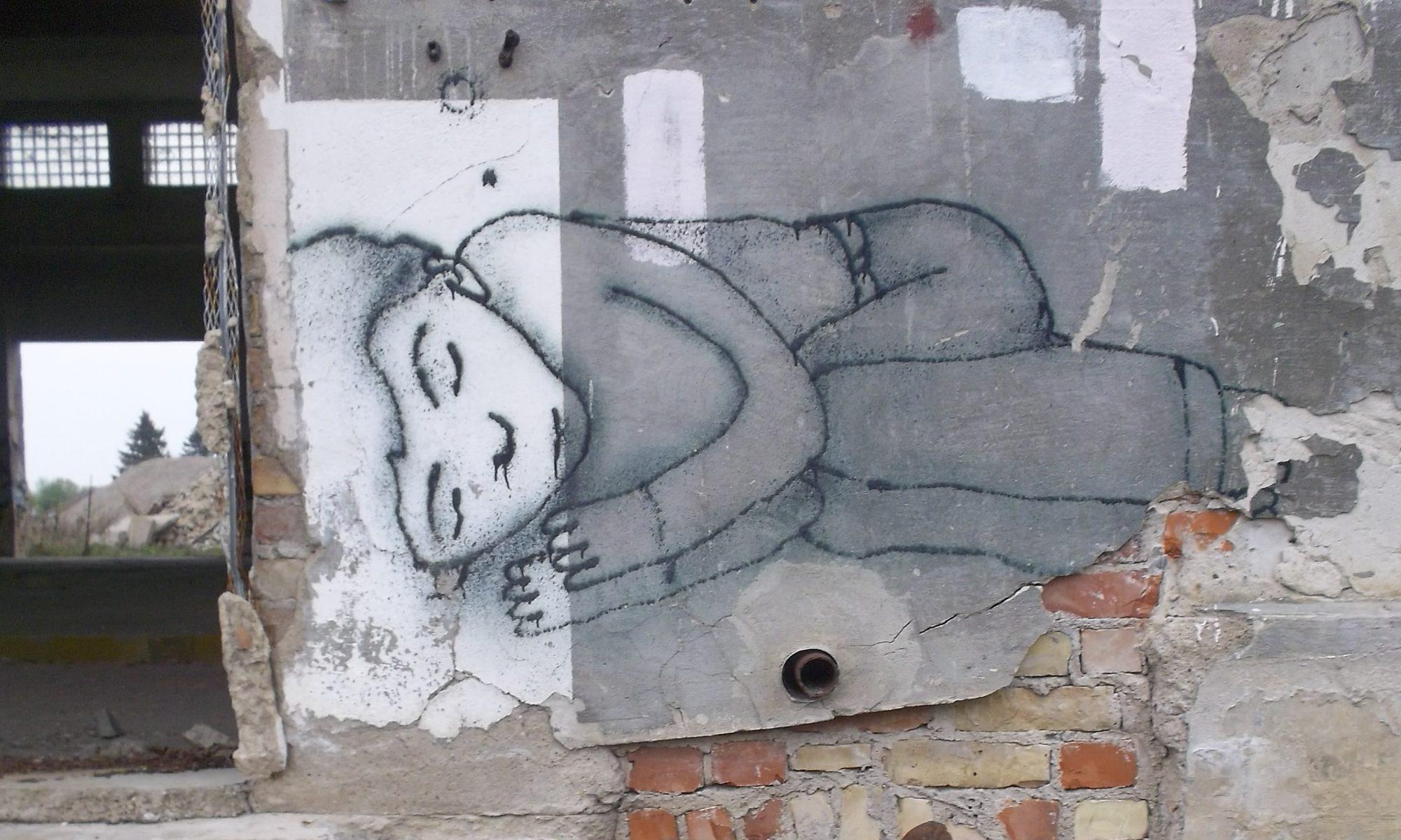 Foto: Grafiti eine schlafenden Person auf einer Bauruine