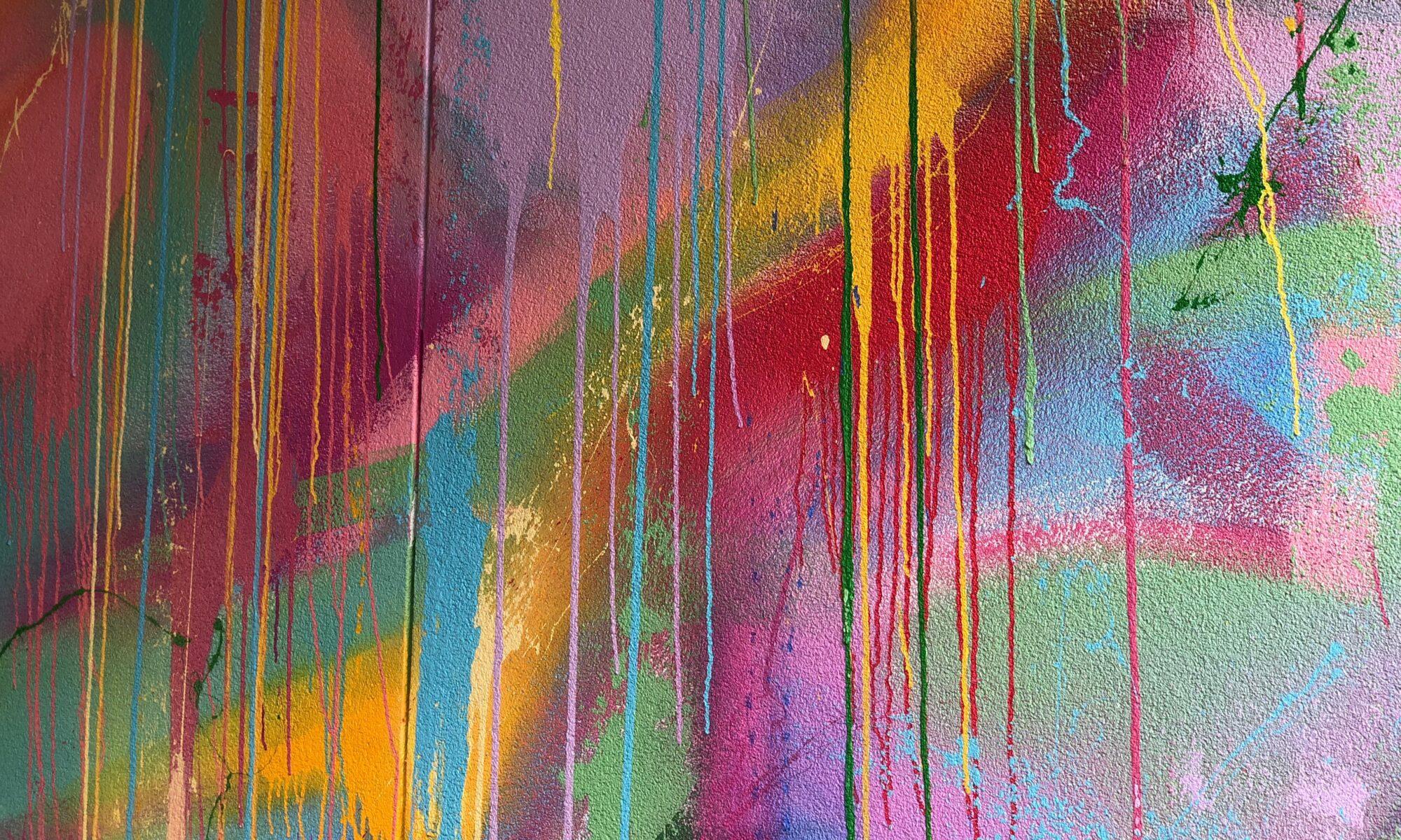 Bunte, besprühte Wand mit verlaufener Graffitifarbe. (Photo by Renee Fisher on Unsplash)