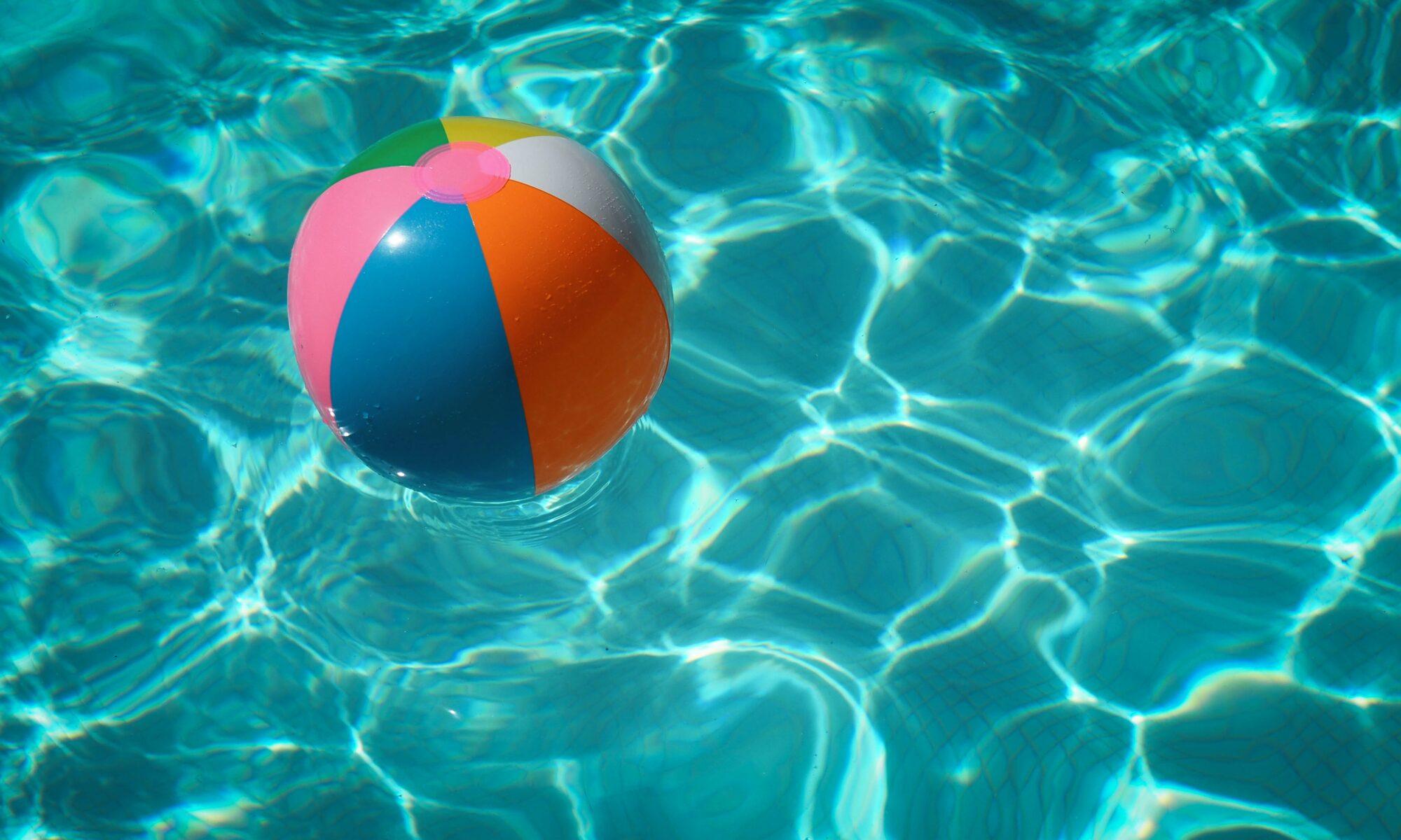 Wasser in einem Freibadbecken, auf dem ein bunter Wasserball schwimmt.